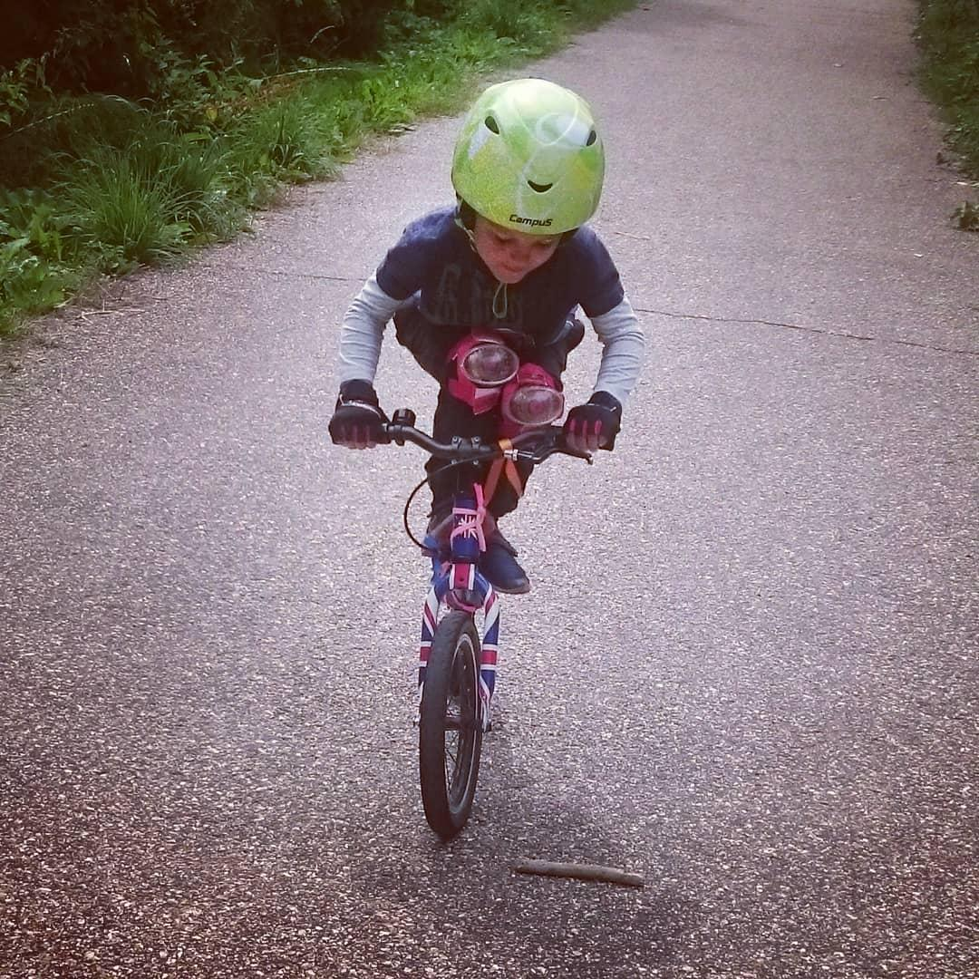 small boy standing on the top tube of his balance bike practicing bike skills taken by instagram @ habwright