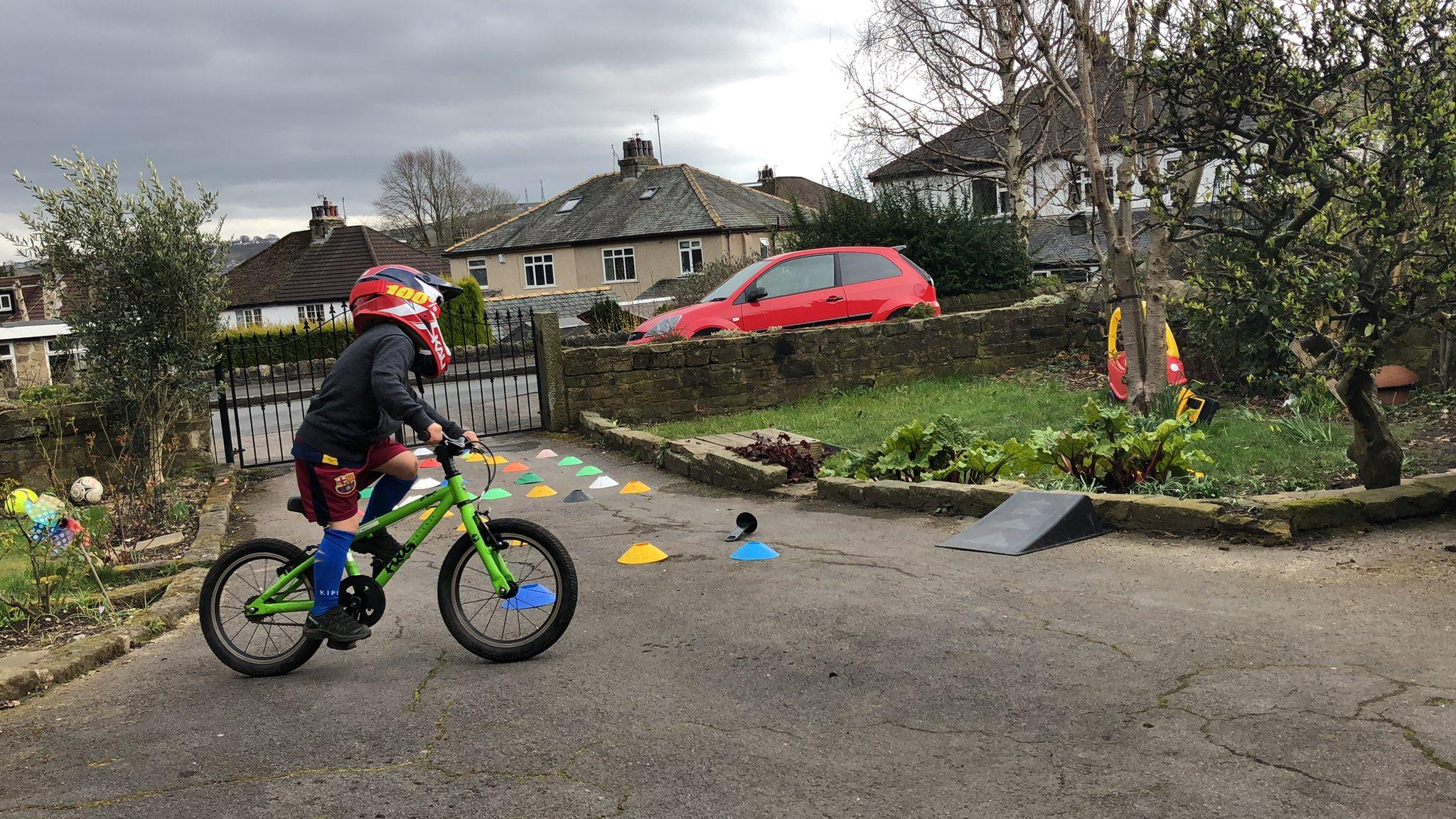 picture of emily groves son riding around cones in a back garden bike skills course set up by emily
