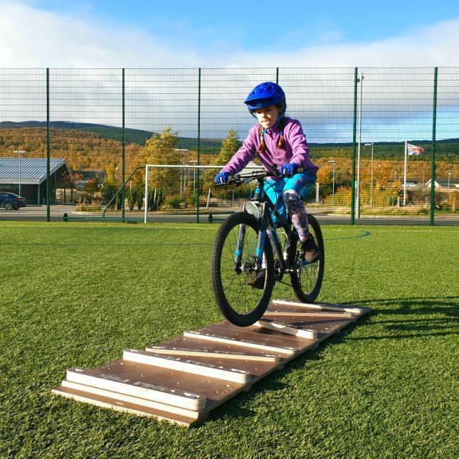 child on bike taking off from a ramp