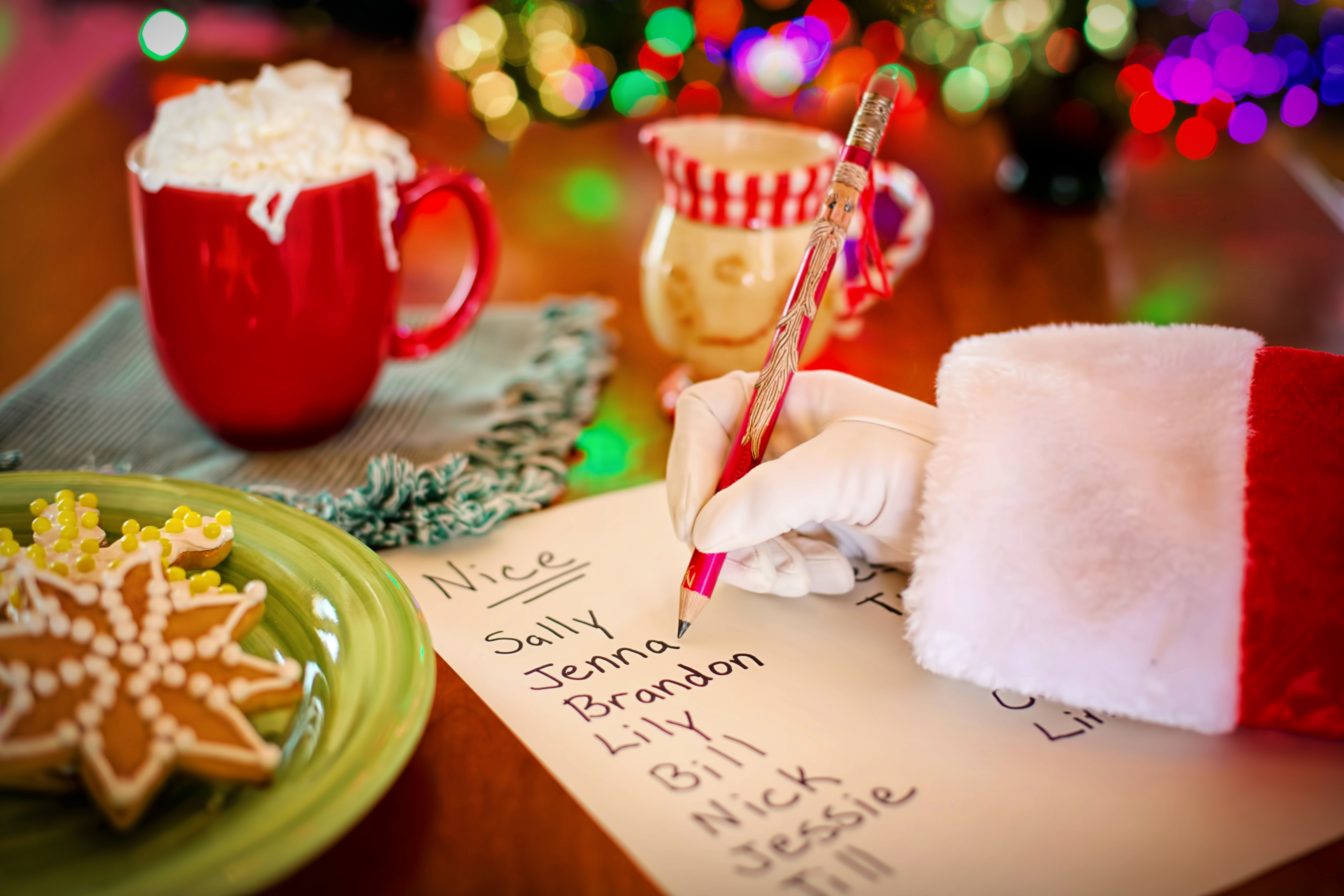 santa sleeve and hand writing a list of childrens names