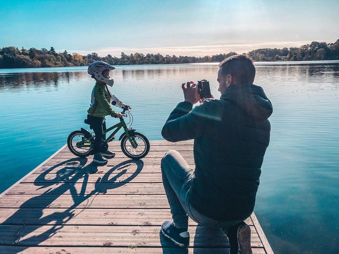 Dad taking a picture of his son on a bike at the edge of a lake taken by Instagram @dad_life_with_the_austins