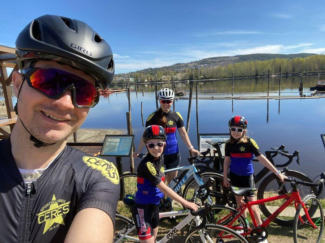 Dad taking a selfie photo with daughters and wife in cycling kit by a lake all on their road bikes