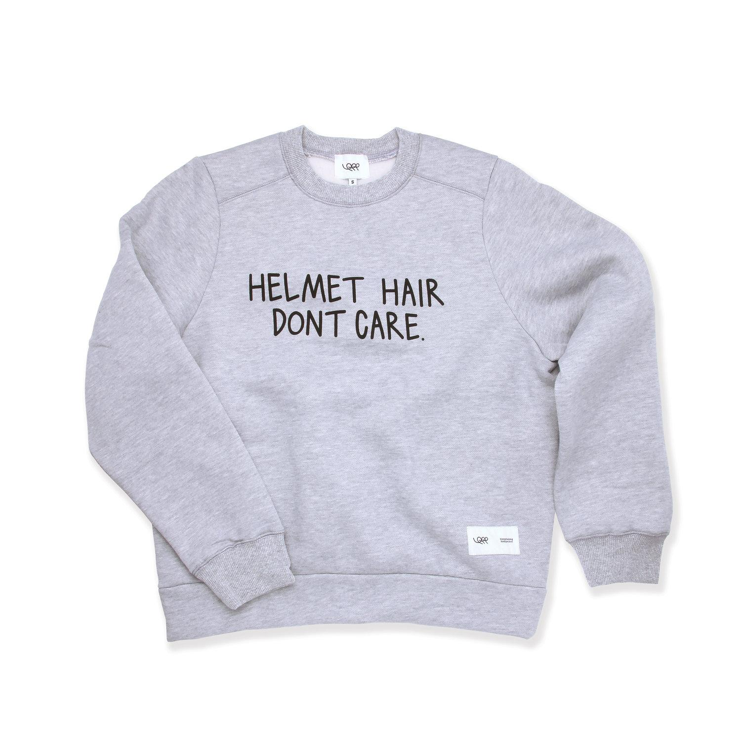 grey jumper with helmet hair don't care written on the front in black writing