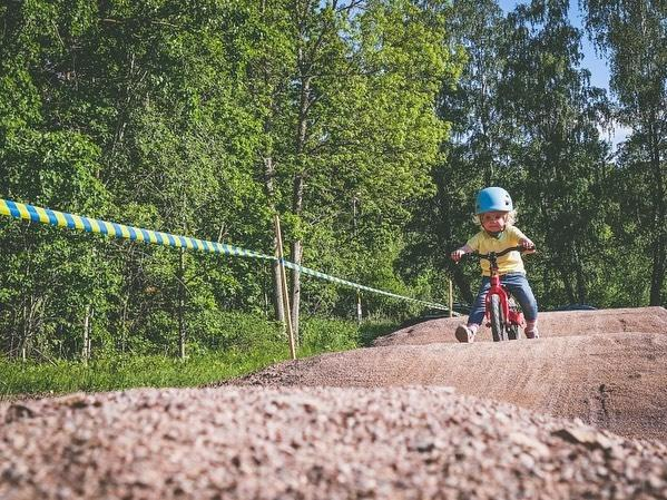 toddler on her balance bike riding a dusty pump track from instagram@elnadahlstrand