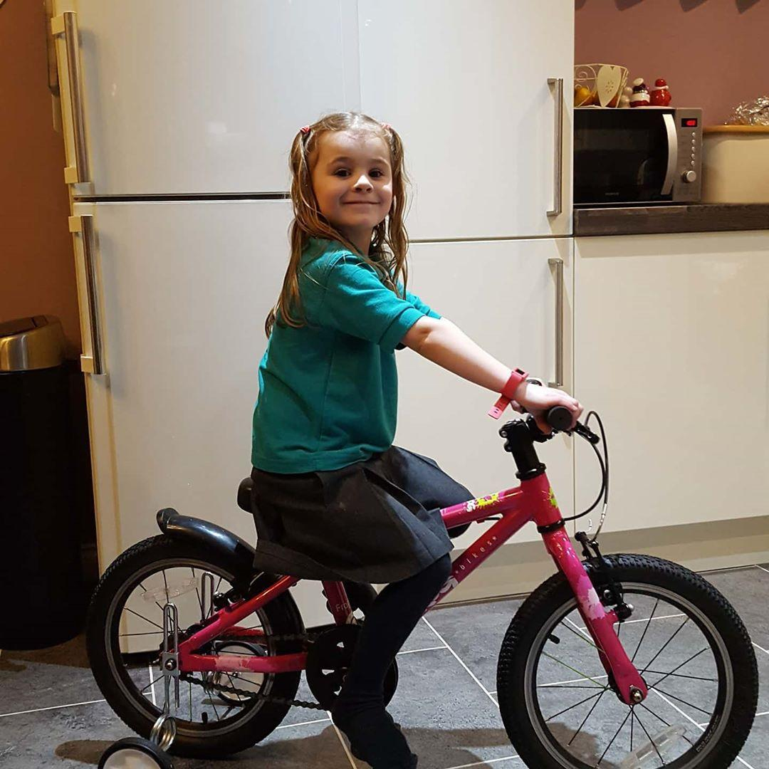 young girl sitting on a bike with stabilisers on in her kitchen, taken by Instagram account @Dalehall2810