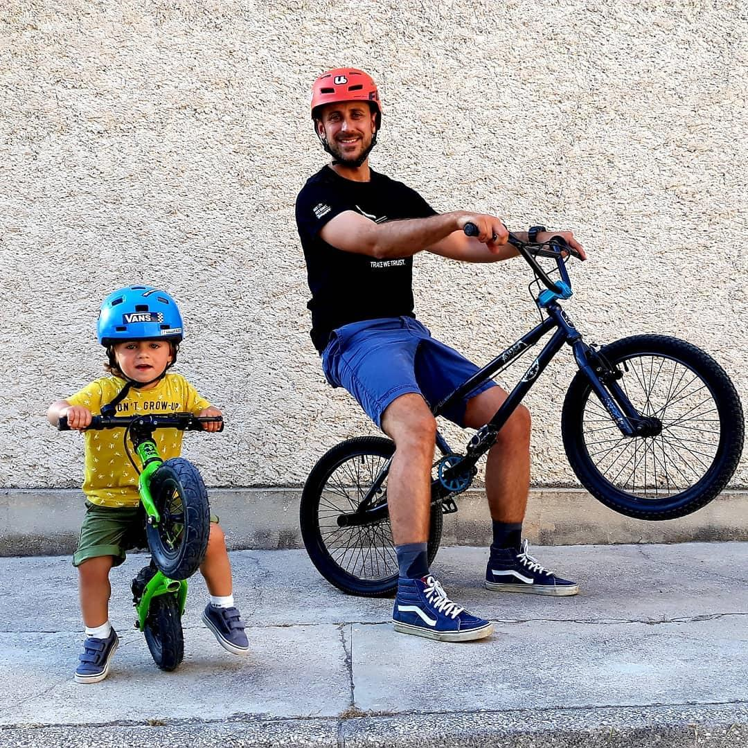 Instagram @leonardonbike toddler on balance bike doing a wheelie with dad in the background pulling a wheelie on his mountain bike