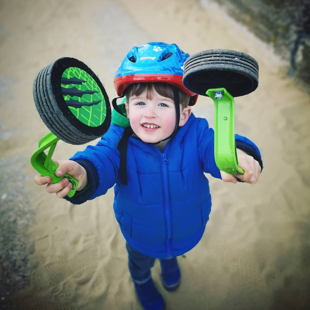 little boy holding stabilisers in the air after they have been taken off his bike, taken by instagram @danciminera