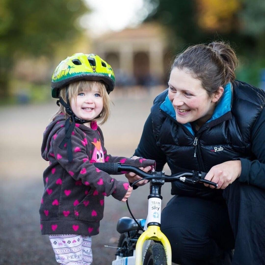emily groves cycle coach crouching next to a young toddler with her balance bike