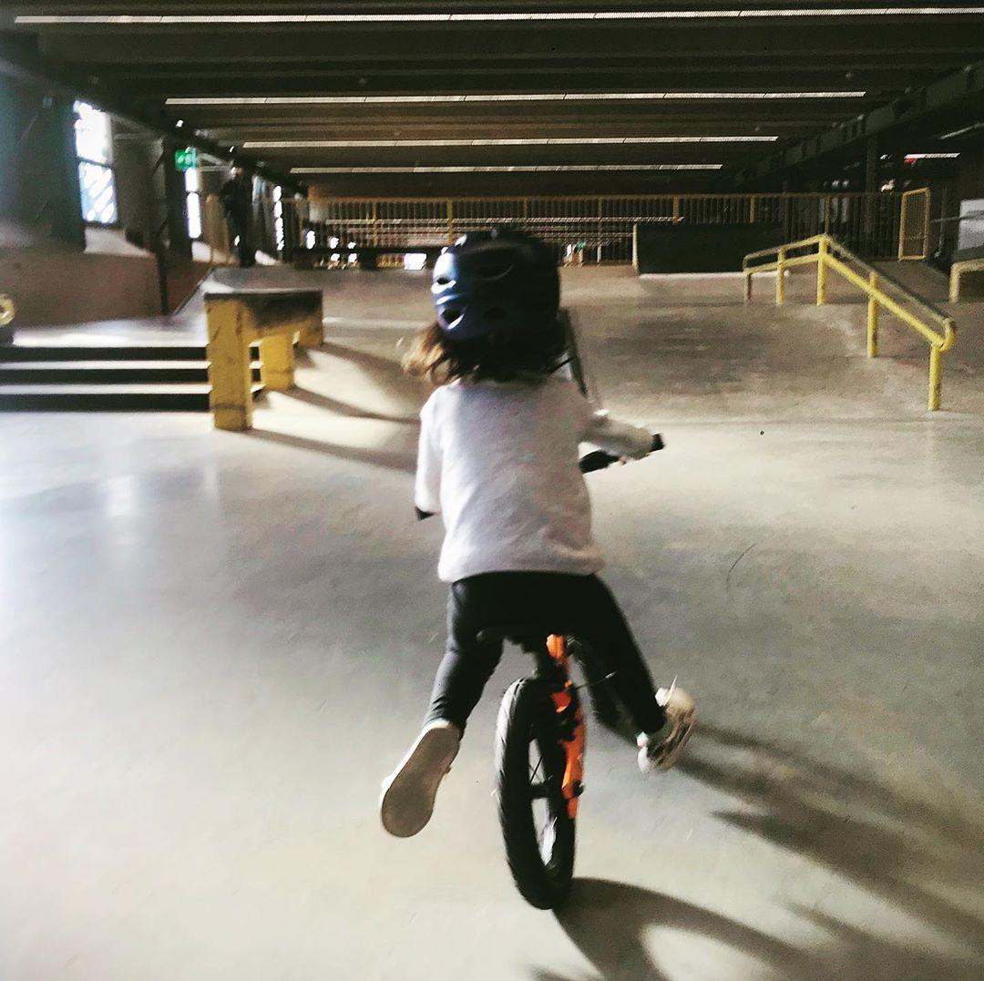 Instagram @joemac76 young toddler gliding on her balance bike in an indoor bike park