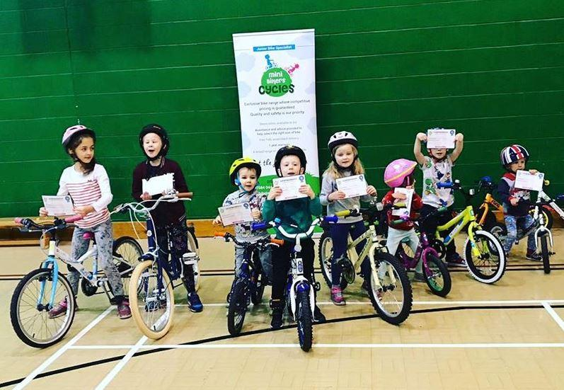 group of young children on balance bikes in a sports hall showing their certificates for their cycle training course