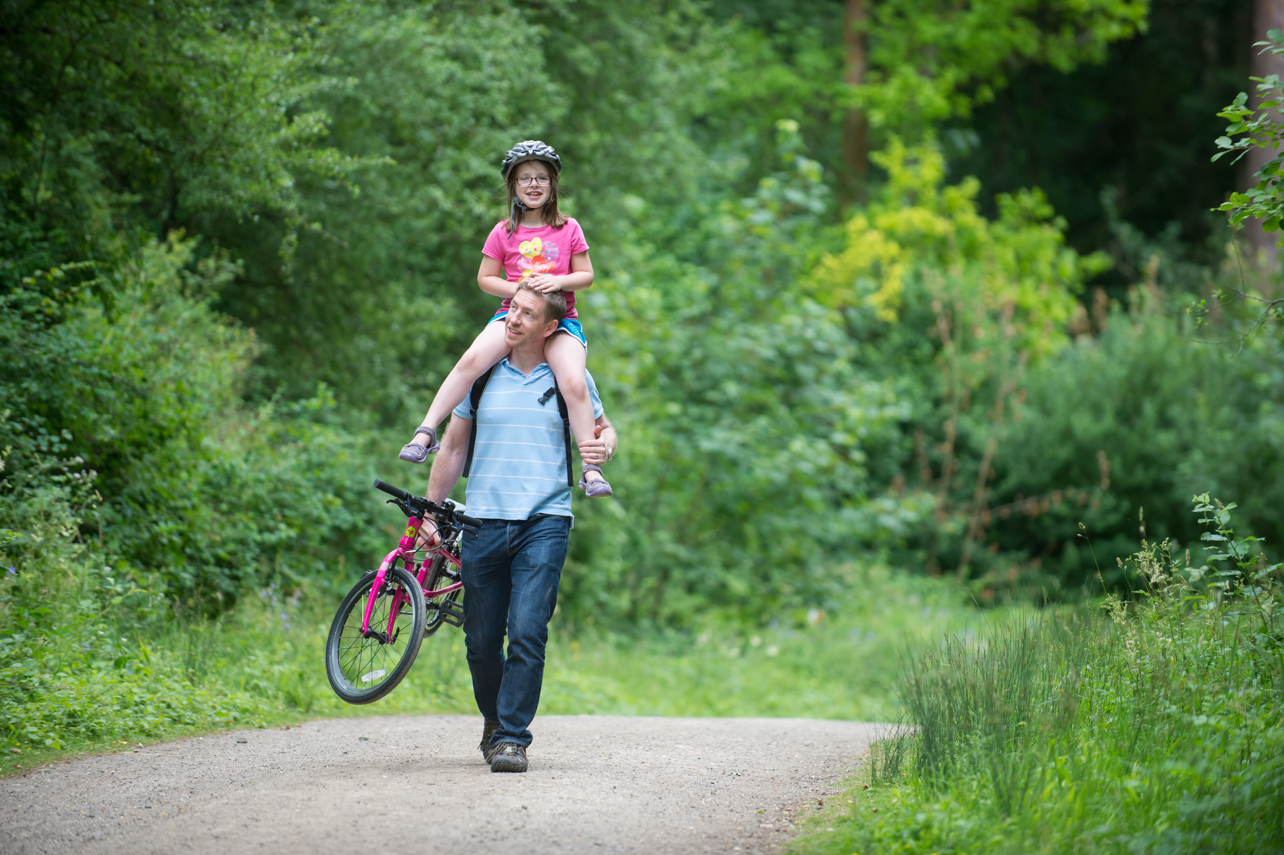 dad carrying daughter and bike
