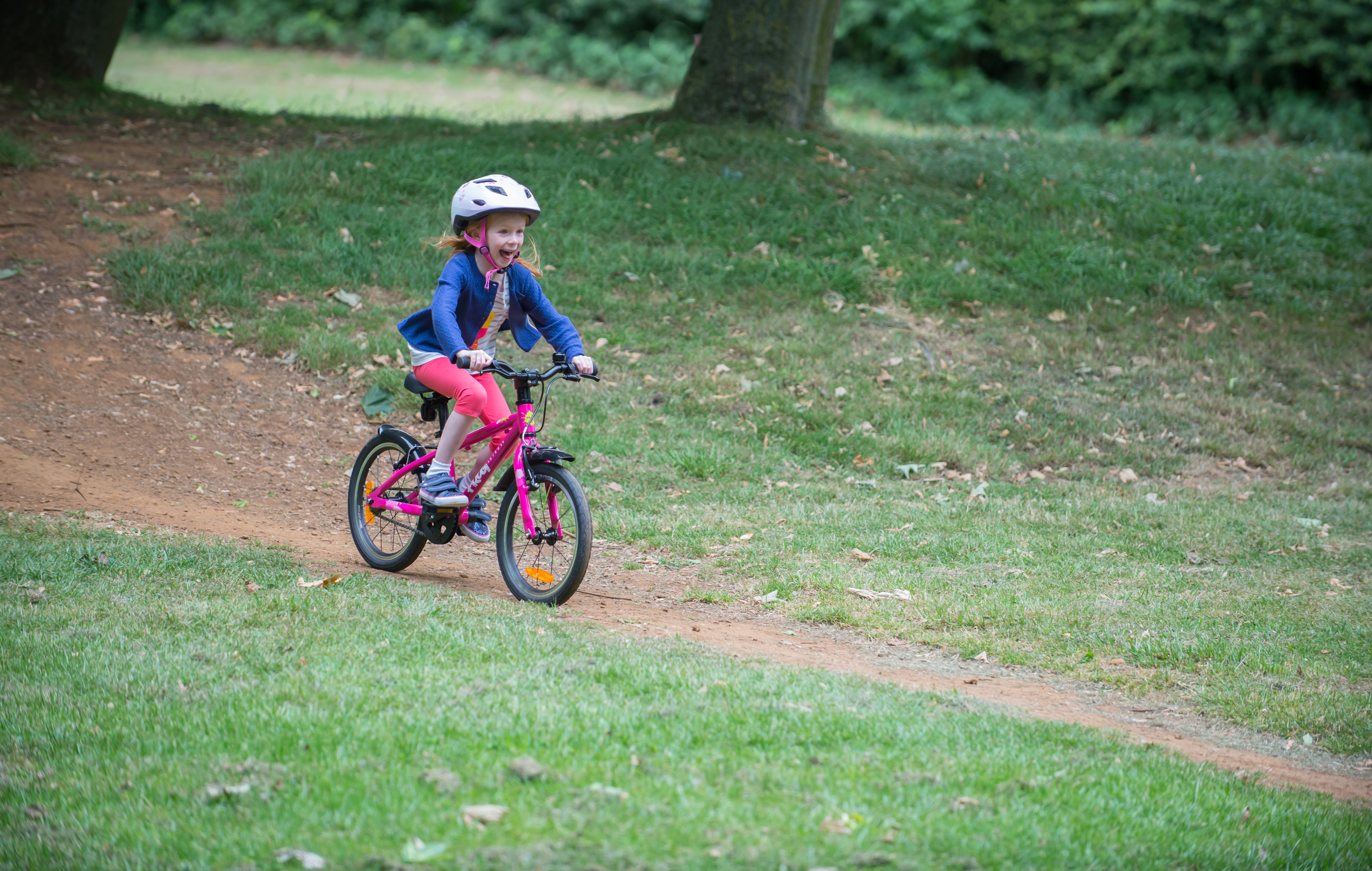 Young girl on a Frog Bike in a park flying down a hill on her bike smiling