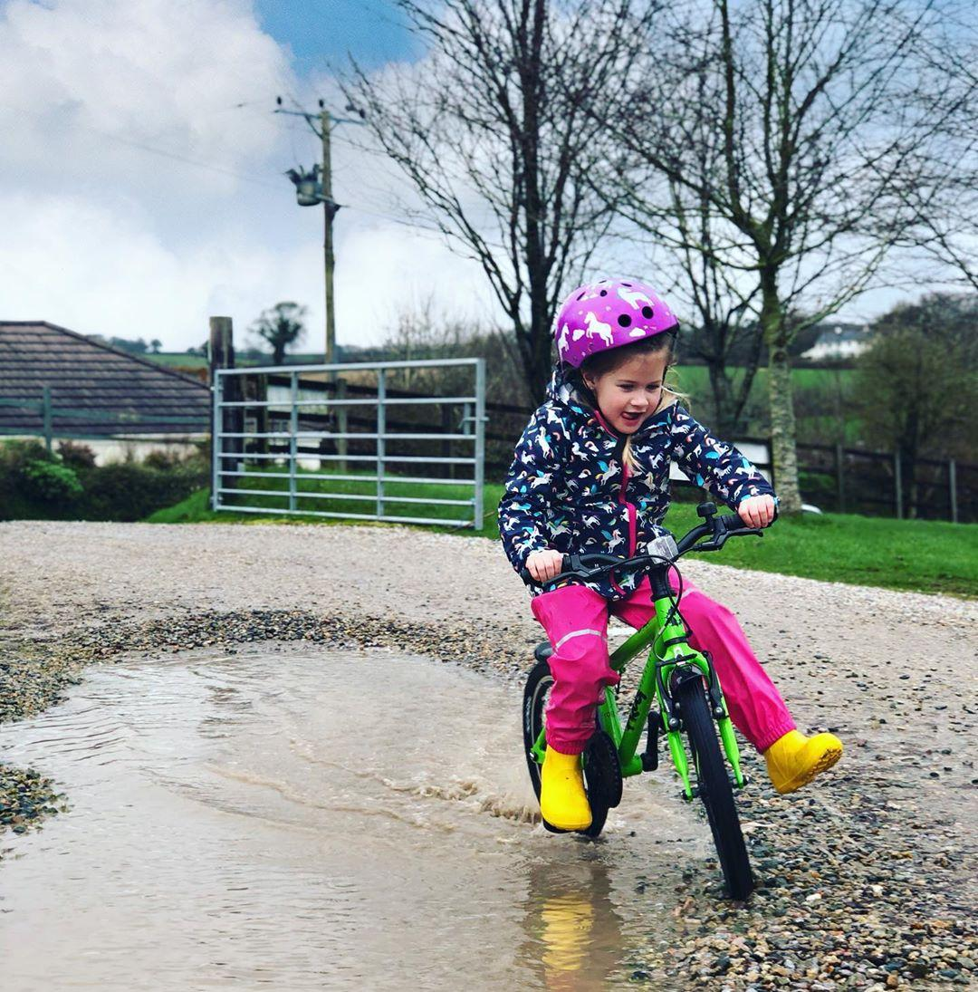 child cycling with only one foot on the pedals and smiling taken by instagram @kids_life_coastal