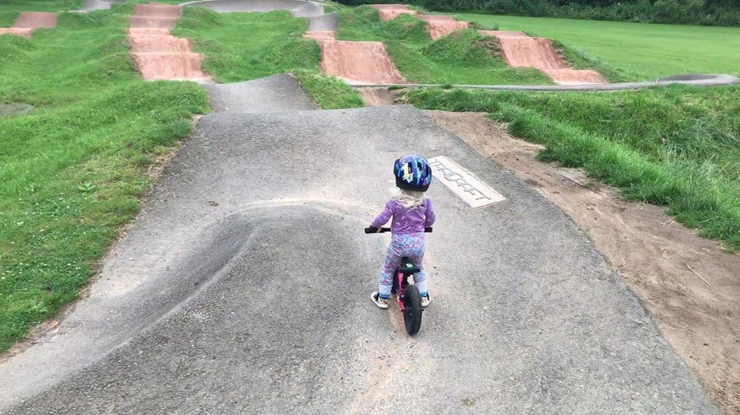 young child sitting on her bike looking out at a large pump track looking like she is about to ride in. taken by instagram @ kidstothefront