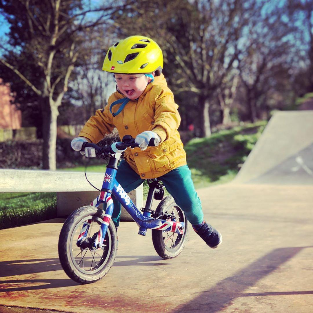 young boy scooting along on his balance bike with legs off the floor having fun. taken by instagram @ kayla_chatt07