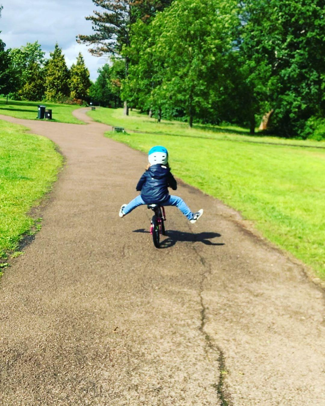 young girl scooting along on her balance bike in the park with both legs off the floor having fun. taken by instagram @ kit_in_the_city