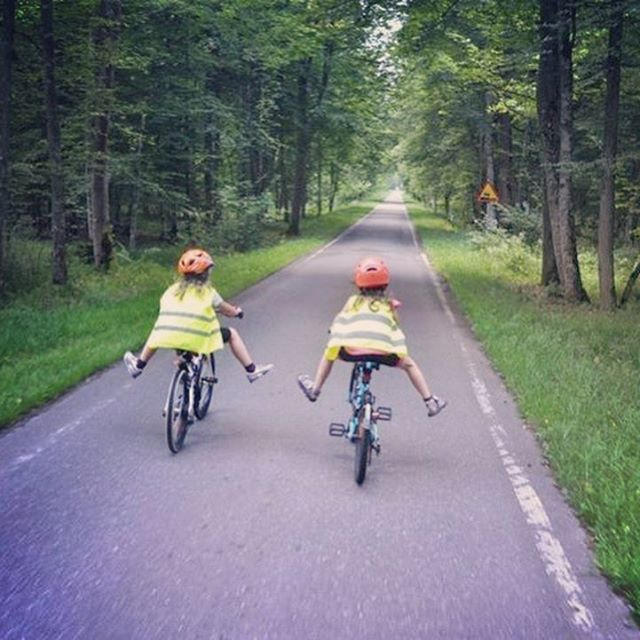 kid friends cycling together in the countryside