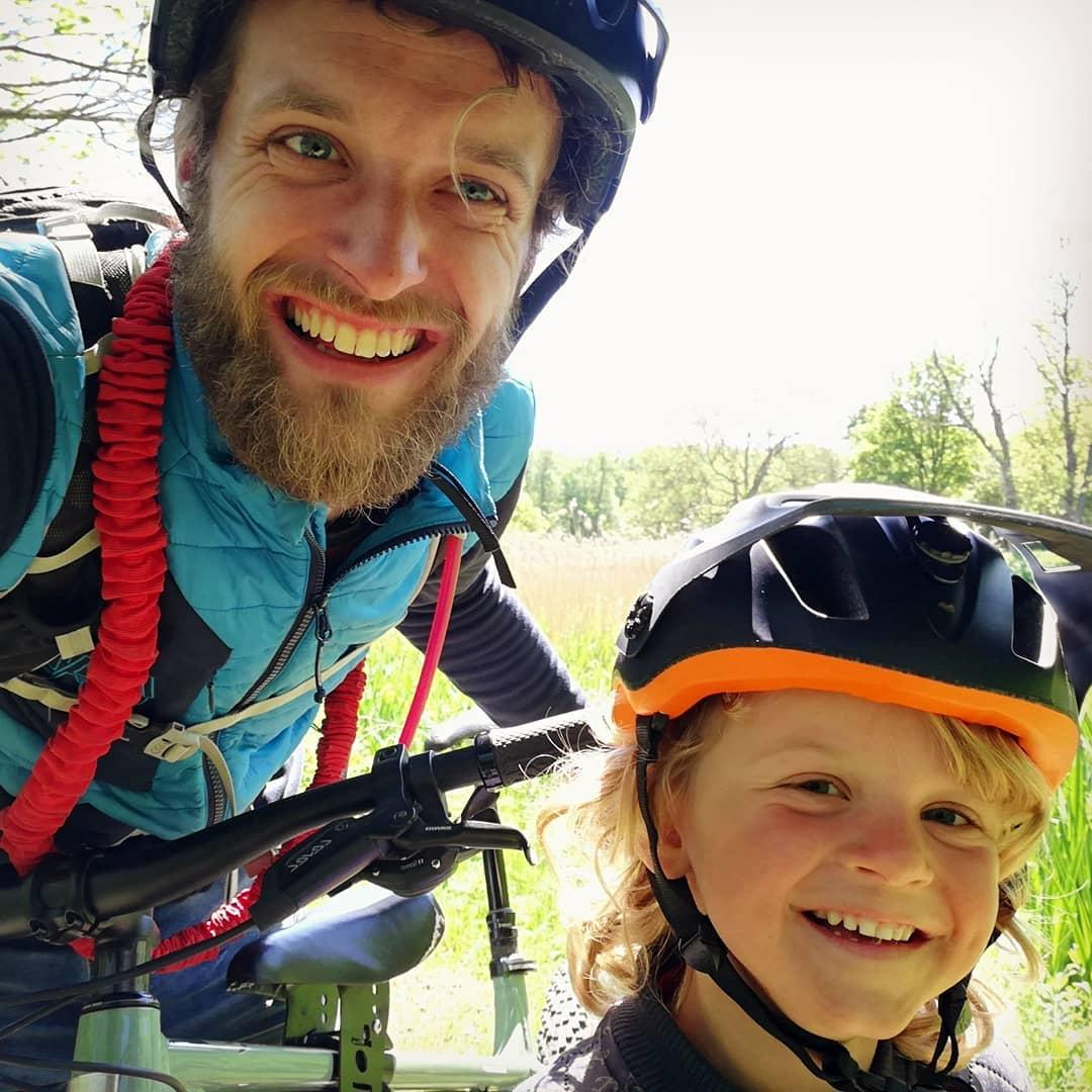 Dad and son smiling together,dad has a tow whee cord over his shoulder, taken by instagram @kristianskjodt
